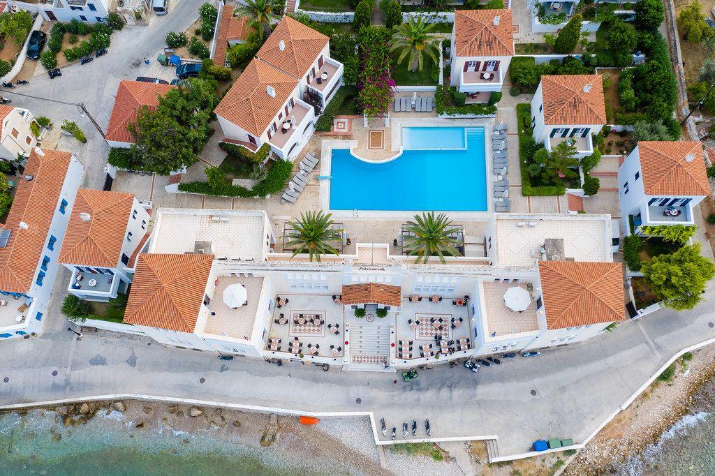 Luftbild zeigt das Hotel Nissia mit Ferienwohnungen und Palmen am eigenen Pool, an der Küste von Spetses