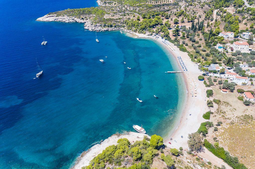 Luftbild zeigt das Meer in mehreren Blautönen und Urlauber auf Booten in der Ferienregion Agii Anargiri auf Spetses