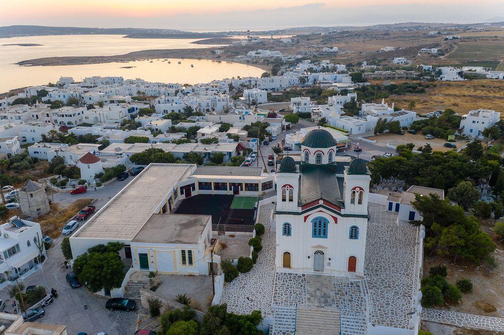 Luftbild zeigt die farbenfrohe Hauptkirche der wunderschönen Hafenstadt Naoussa auf Paros, Griechenland