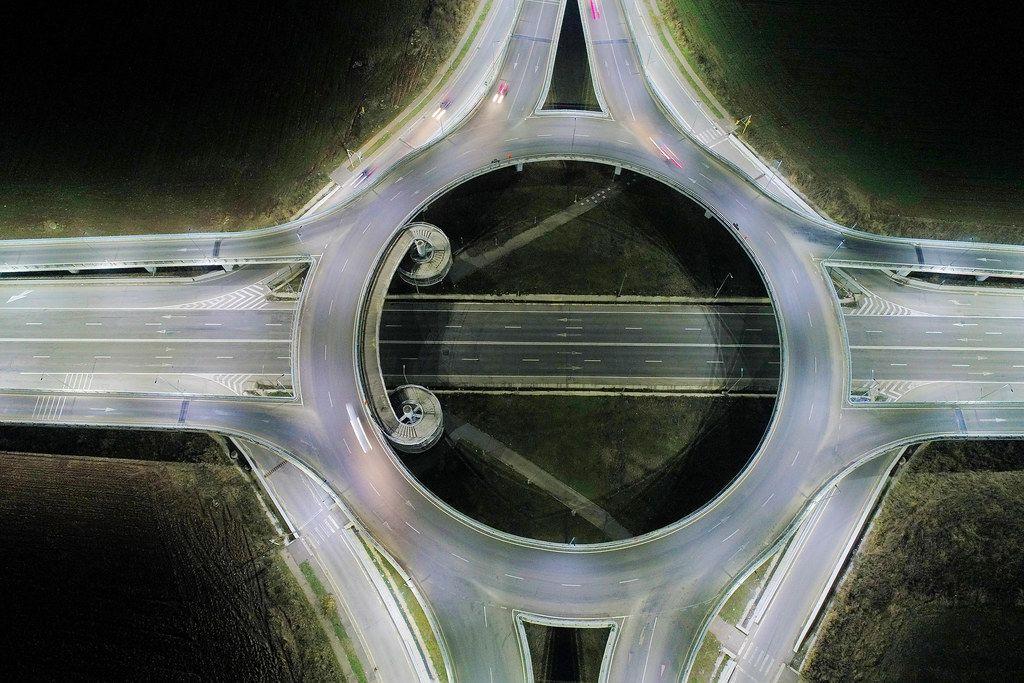 Luftbild zeigt die Nachtansicht eines großen Verkehrskreisels