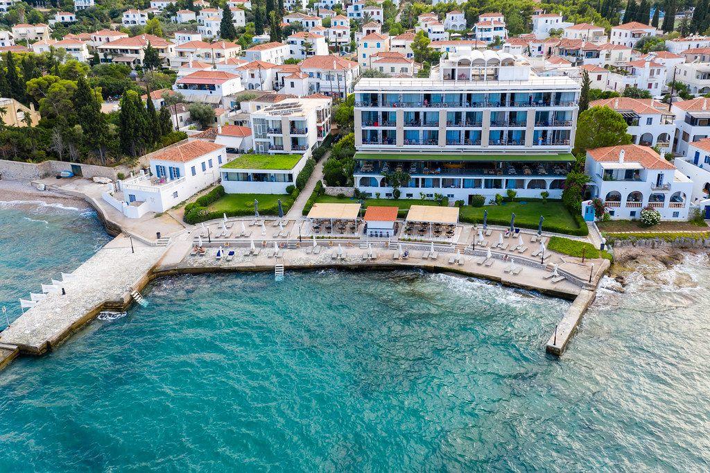 Luftbild zeigt Touristen beim Urlaub auf Balkonen des Spetses Hotels in Griechenland. mit Ausblick auf das grüne Meer