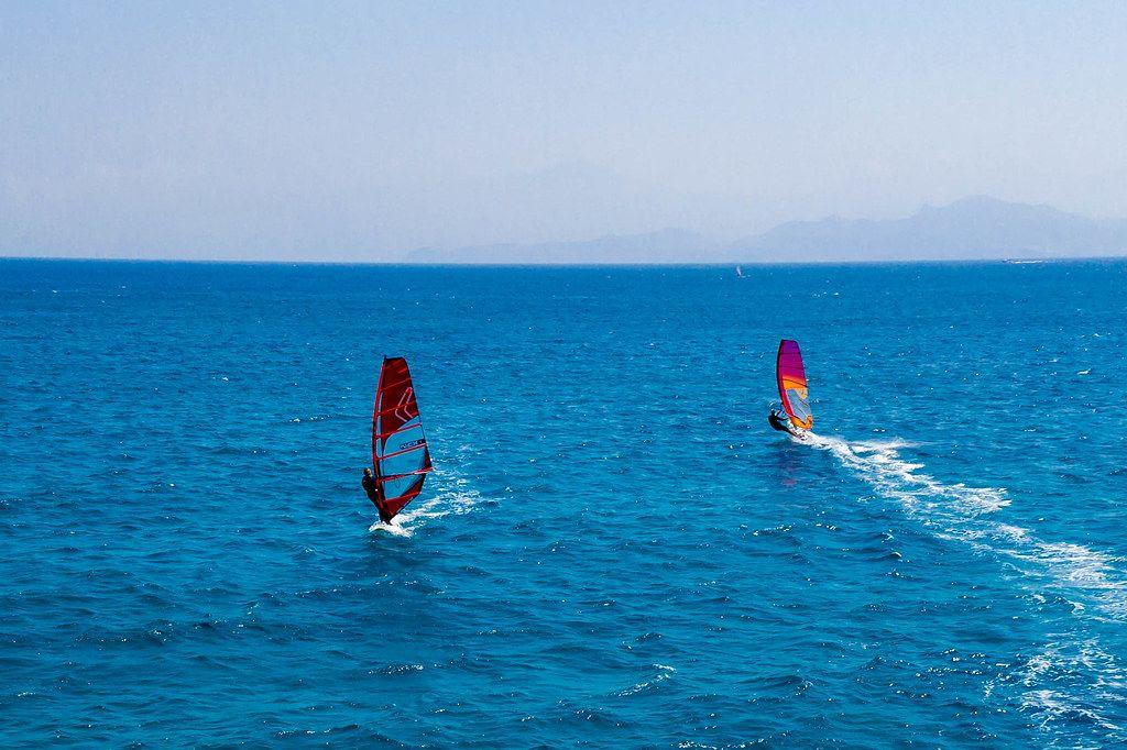 Luftbild zeigt zwei Windsurfer auf dem blauen Meer vor Paros, Griechenland, in der Ägäis