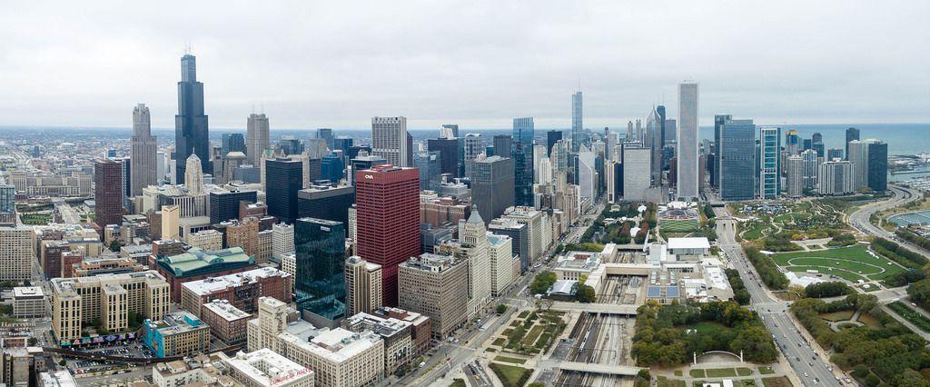 Luftbildpanorama: Grant Park und rotes Gebäude CNA Center inmitten von Chicagos Skyline