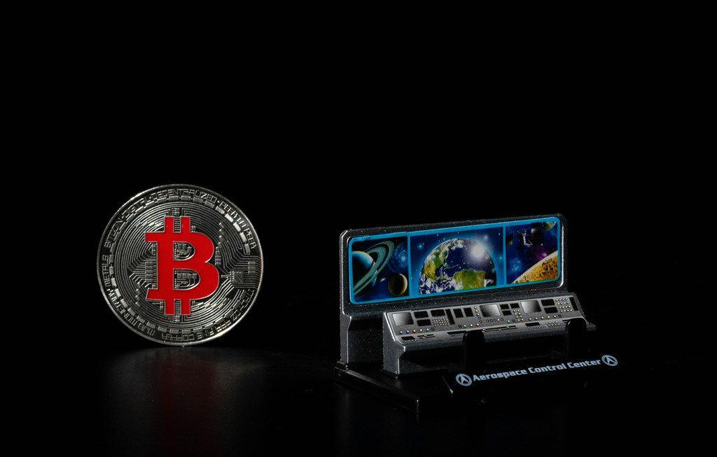 Luftfahrtkontrollzentrum und silberner Bitcoin auf schwarzem Hintergrund
