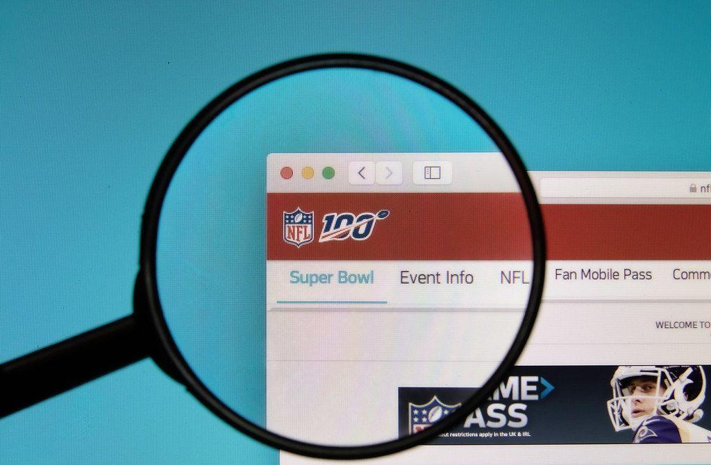 Lupe über NFL-Logo auf Hompage der National Football League, dem Veranstalter des Super Bowl