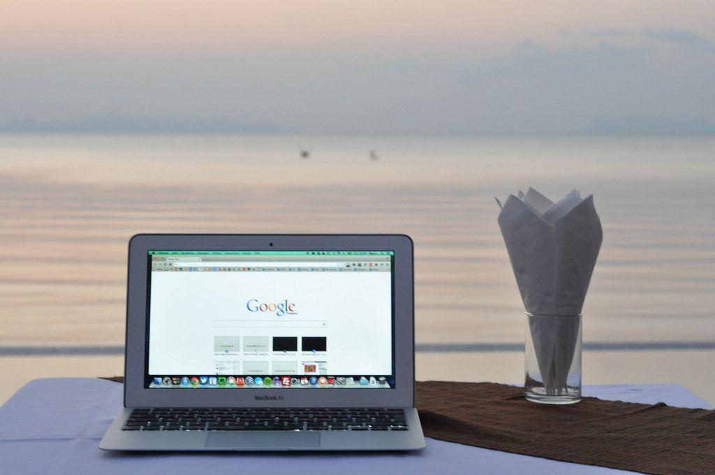 MacBook Air mit geöffneter Google-Suche, Meer im Hintergrund