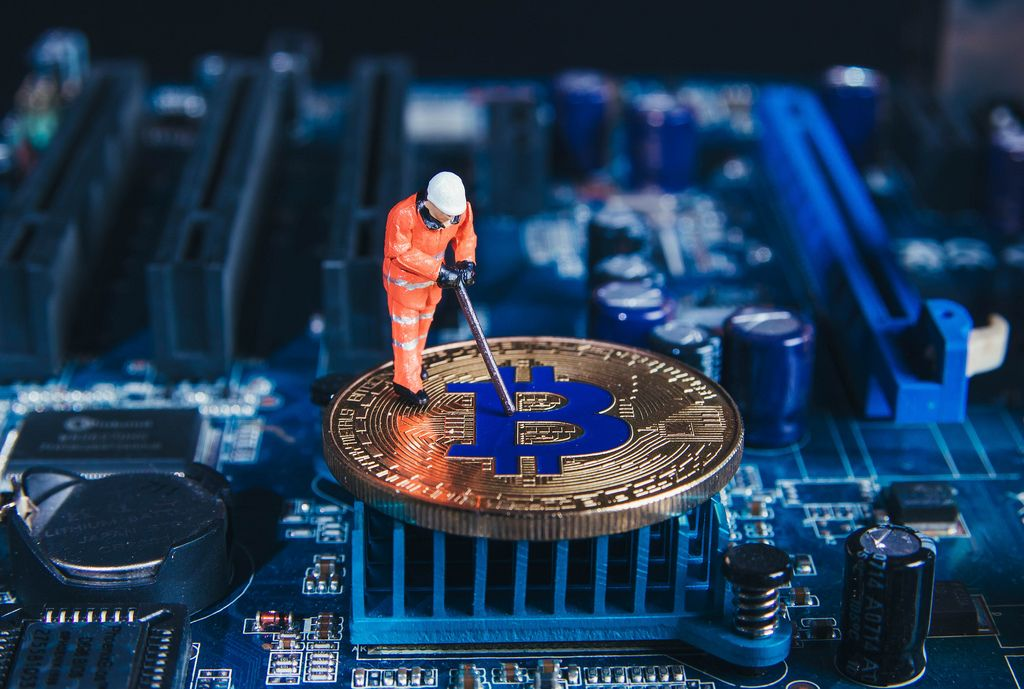 Macro miner figure working on a Bitcoin on computer motherboard