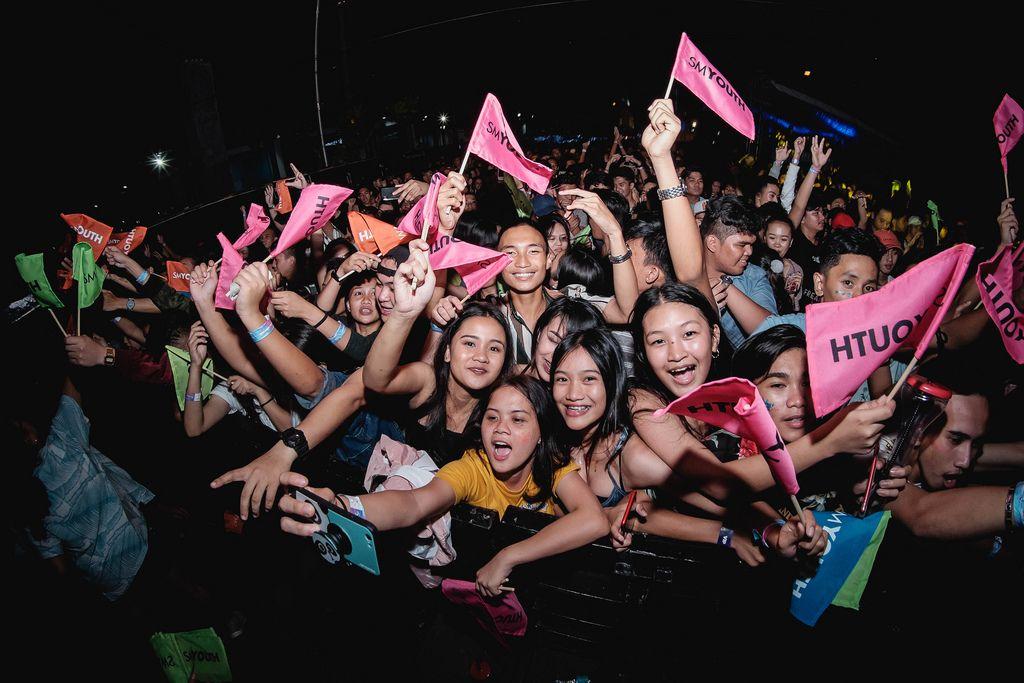 Mädchen feiern mit rosaroten Fahnen in Menschenmenge am Dinagyang Festival, Philippinen