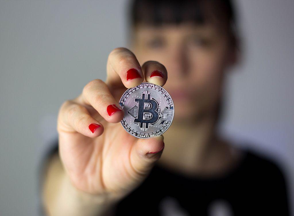 Mädchen hält silbernen Bitcoin in der Hand