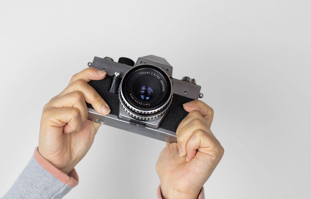 Mädchen mit alter Filmkamera in Händen