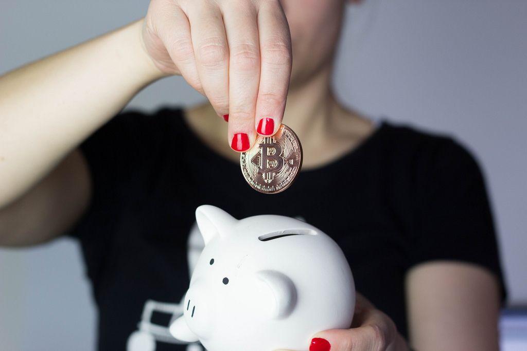 Mädchen steckt Bitcoin ins Sparschwein