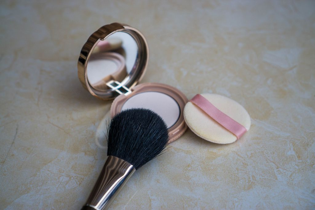 Makeup Brush laying on Powder Box with Mirror