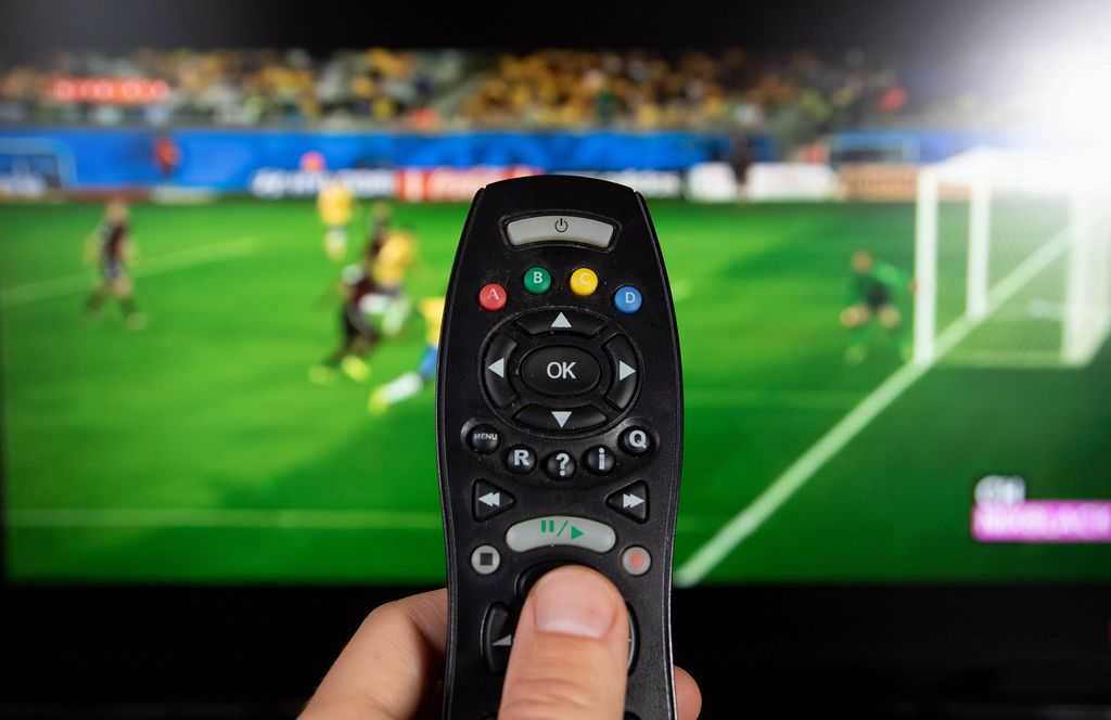 Male hand holding TV remote control.jpg