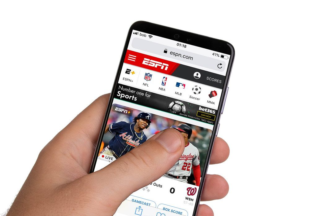 Male hands holding smartphone with an open ESPN website