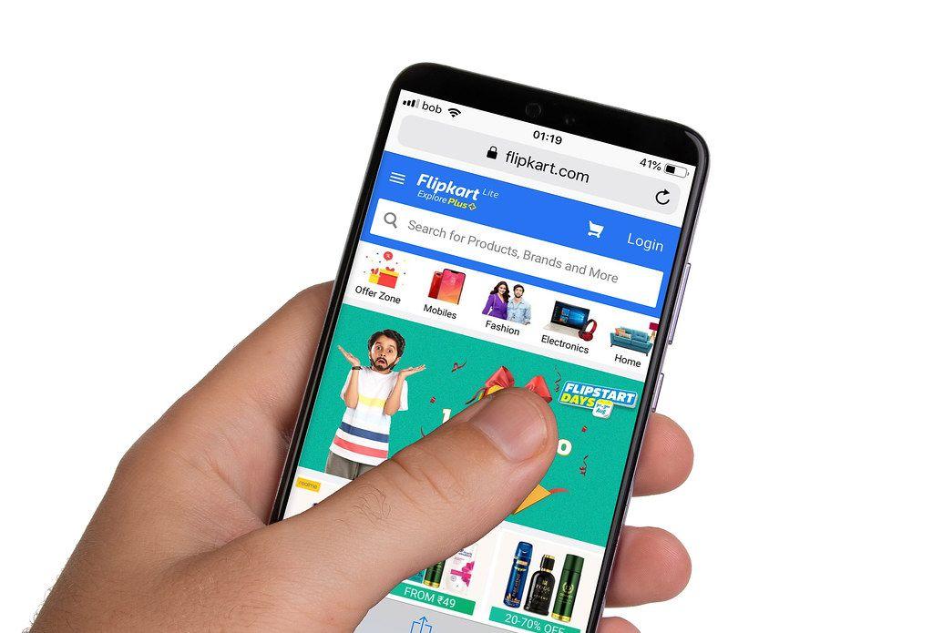 Male hands holding smartphone with an open Flipkart website