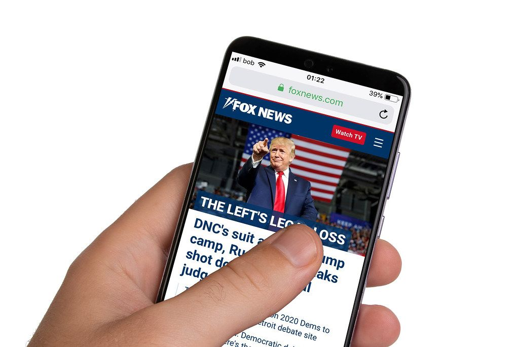 Male hands holding smartphone with an open Fox News website