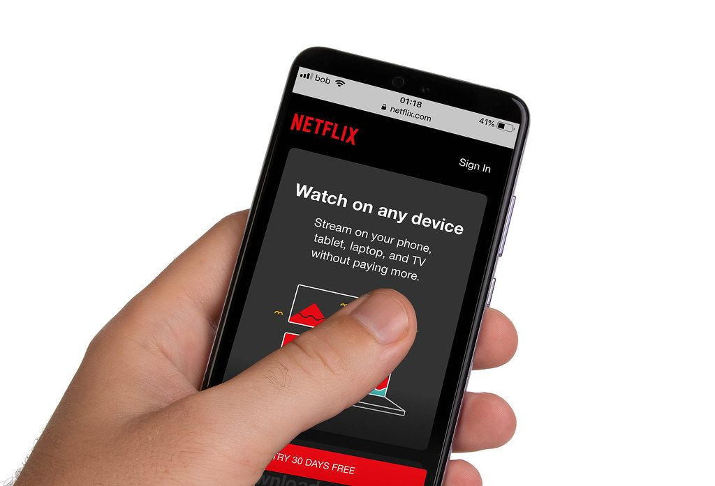 Male hands holding smartphone with an open Netflix application