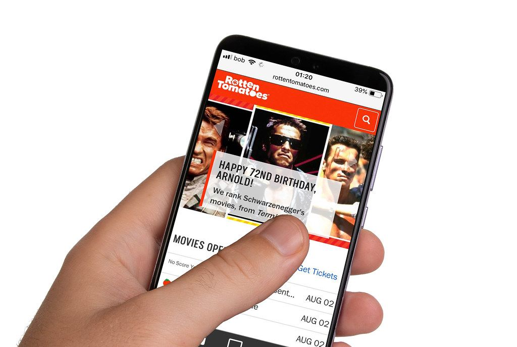 Male hands holding smartphone with an open Rotten Tomatoes website