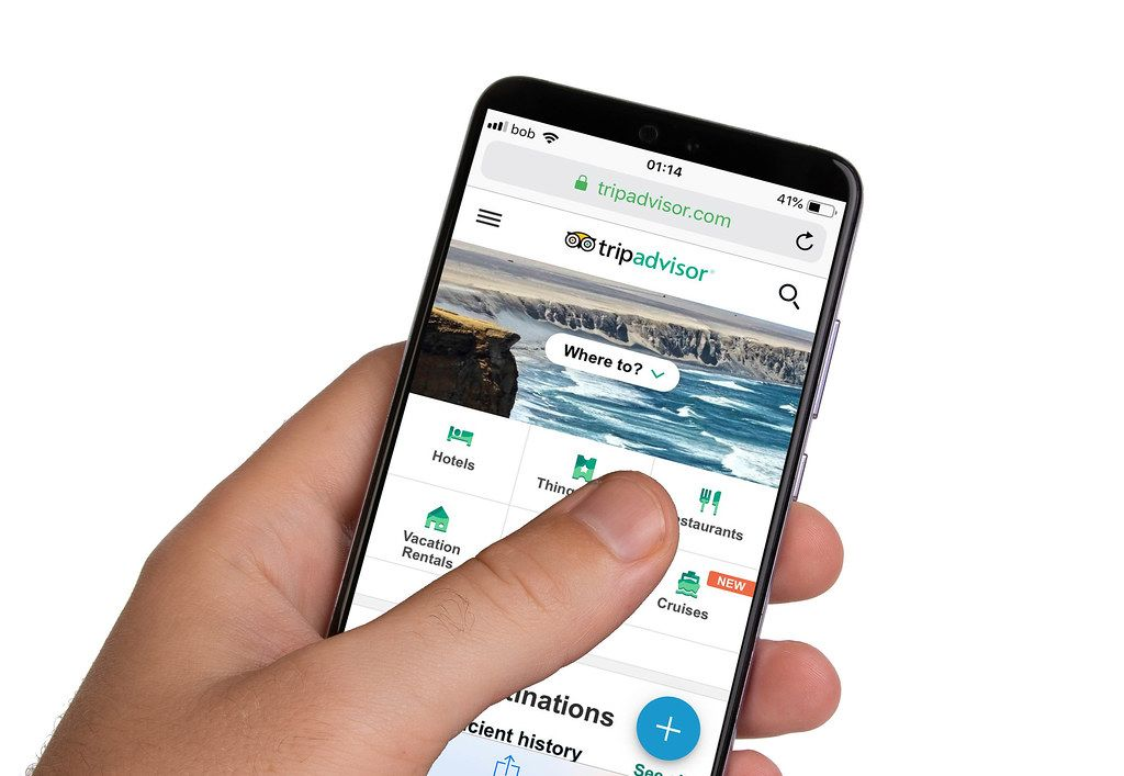 Male hands holding smartphone with an open Tripadvisor application
