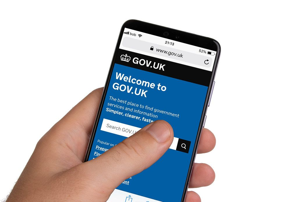 Male hands holding smartphone with an open website of United Kingdom government
