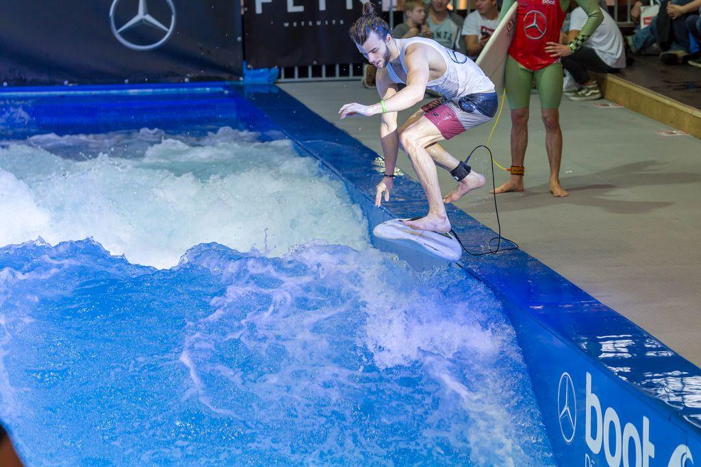 Man catching the permanent wave of the surf machine Citywave at fair Boot Düsseldorf 2018
