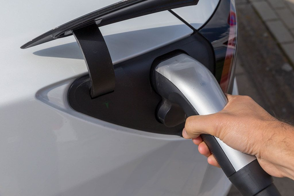 Man charging his electric car Tesla Model 3 with type 2 connector