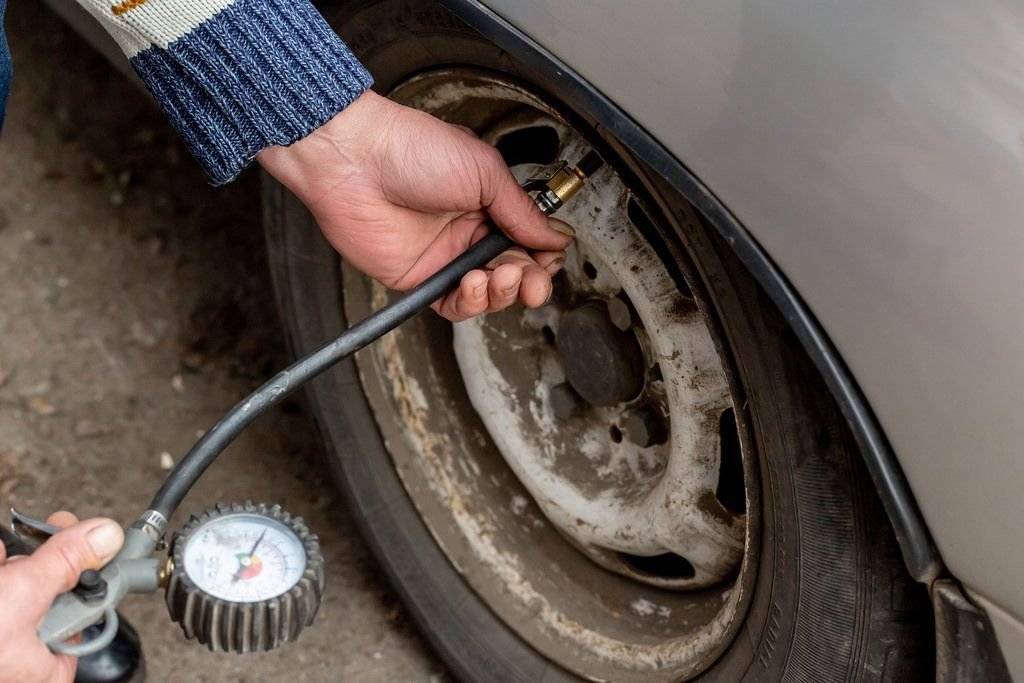 Man checking air pressure and filling air in the tires of his car