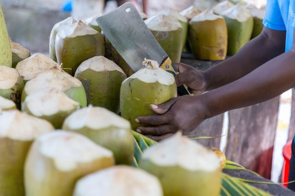 Man cuts open a green coconut with cleaver at Fruita Cabana bar on Anse Source d'Argent Beach in La Digue, Seychelles