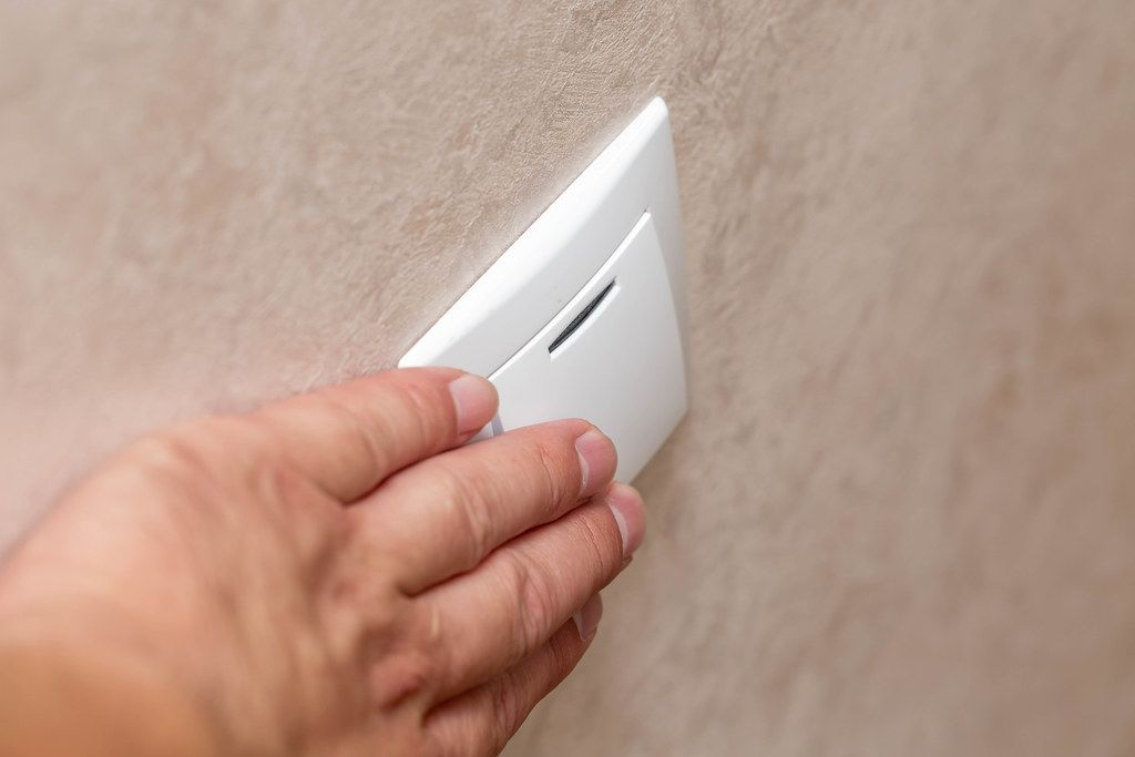 Man hand pressing button for light on wall