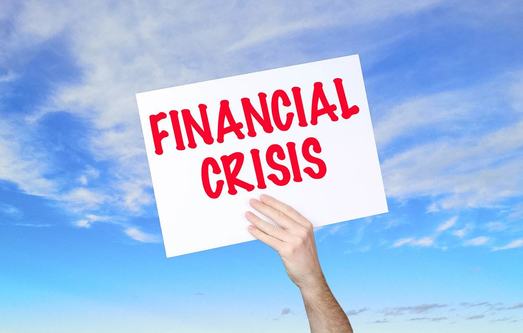 Man holding banner with Financial Crisis text with blue sky background
