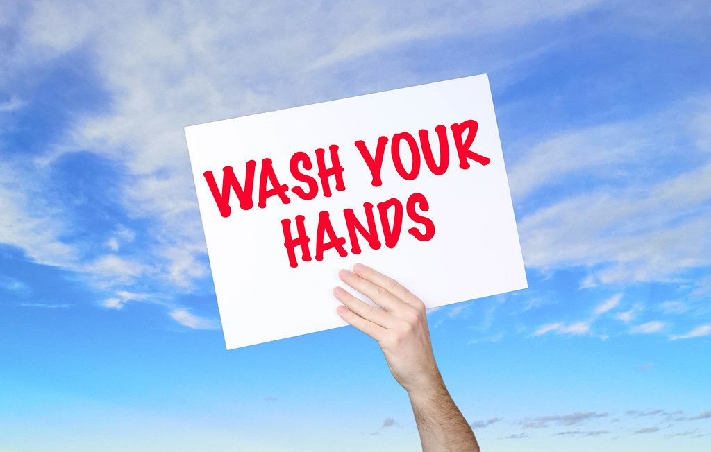 Man holding banner with Wash Your Hands text with blue sky background