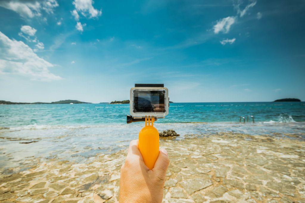 Man holding underwater camera (like GoPro) at the beach