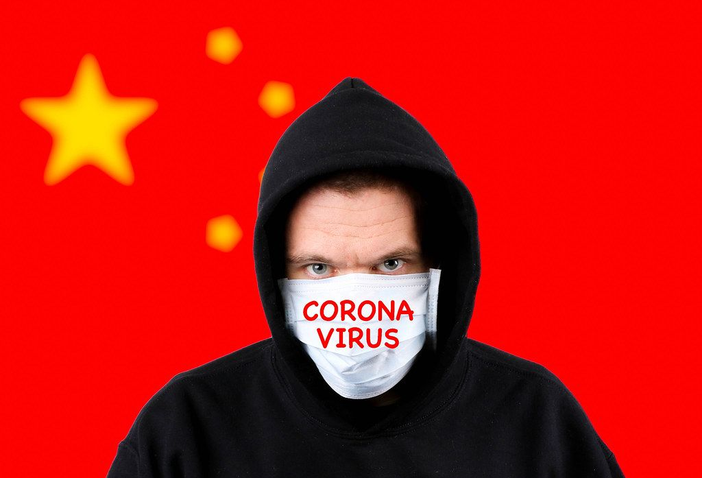 Man in hoodie wearing protection face mask with flag of China