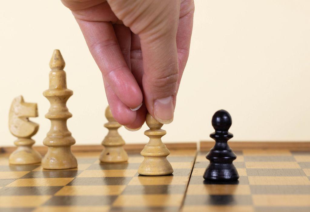 Man makes a move chess pawn