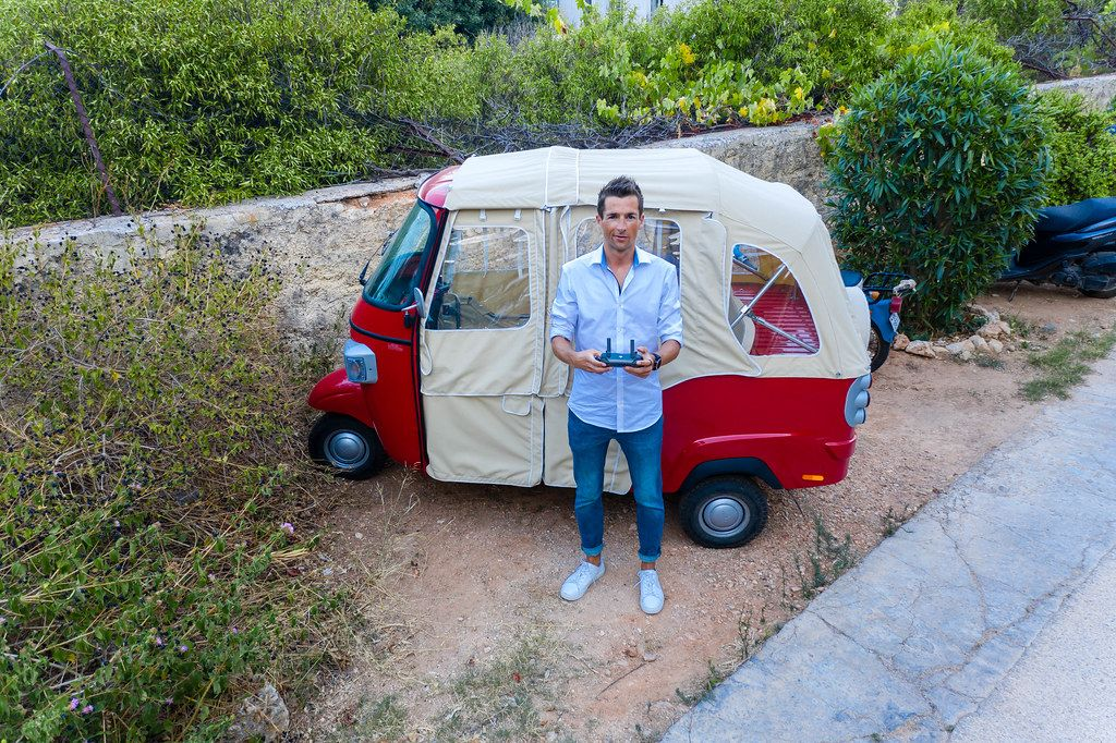 Man takes a drone selfie in front of a funny vehicle on greek Island Spetses