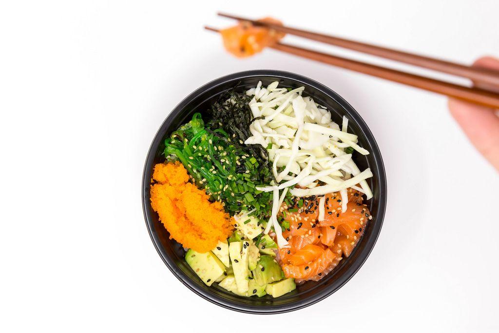 Man takes a piece of with chopsticks from the Poke Salmon Teriyaki Bowl