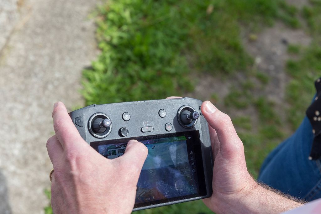 Man uses the black DJI Mavic 2 Smart Controller and drone remote control in the open field