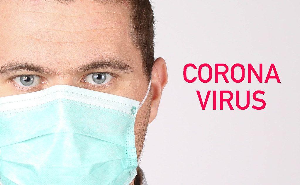 Man wearing face mask on white background with Coronavirus text
