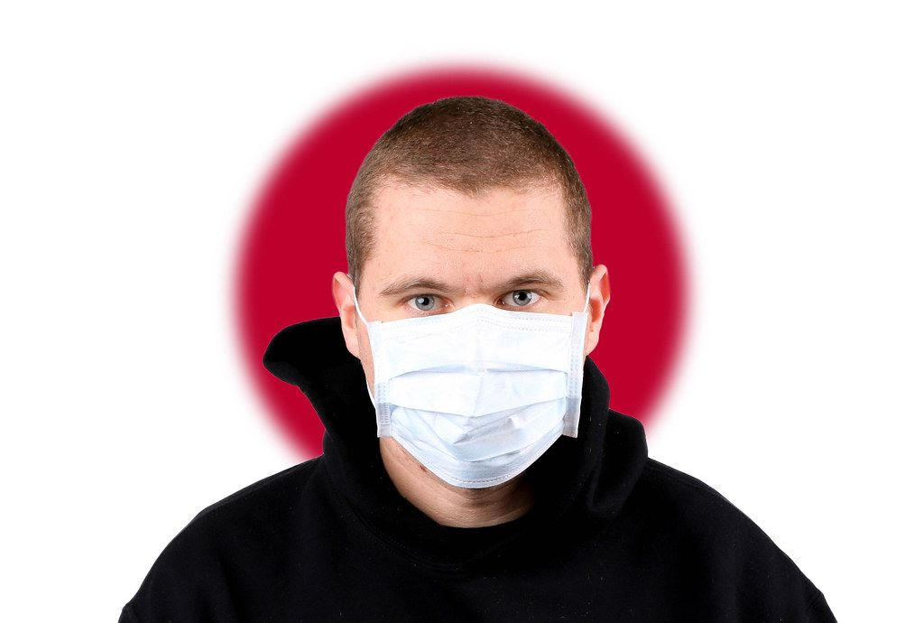 Man wearing protection face mask with flag of Japan
