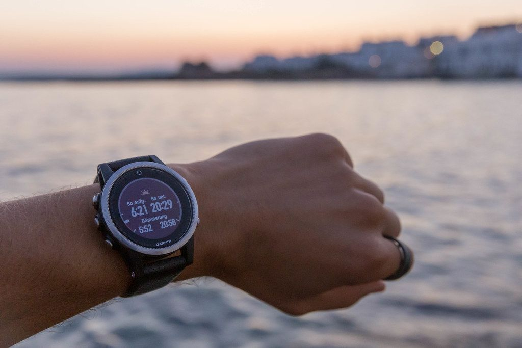 Man wears the Garmin running clock, with sunrise, sunset and twilight time display, in front of the Mediterranean Sea