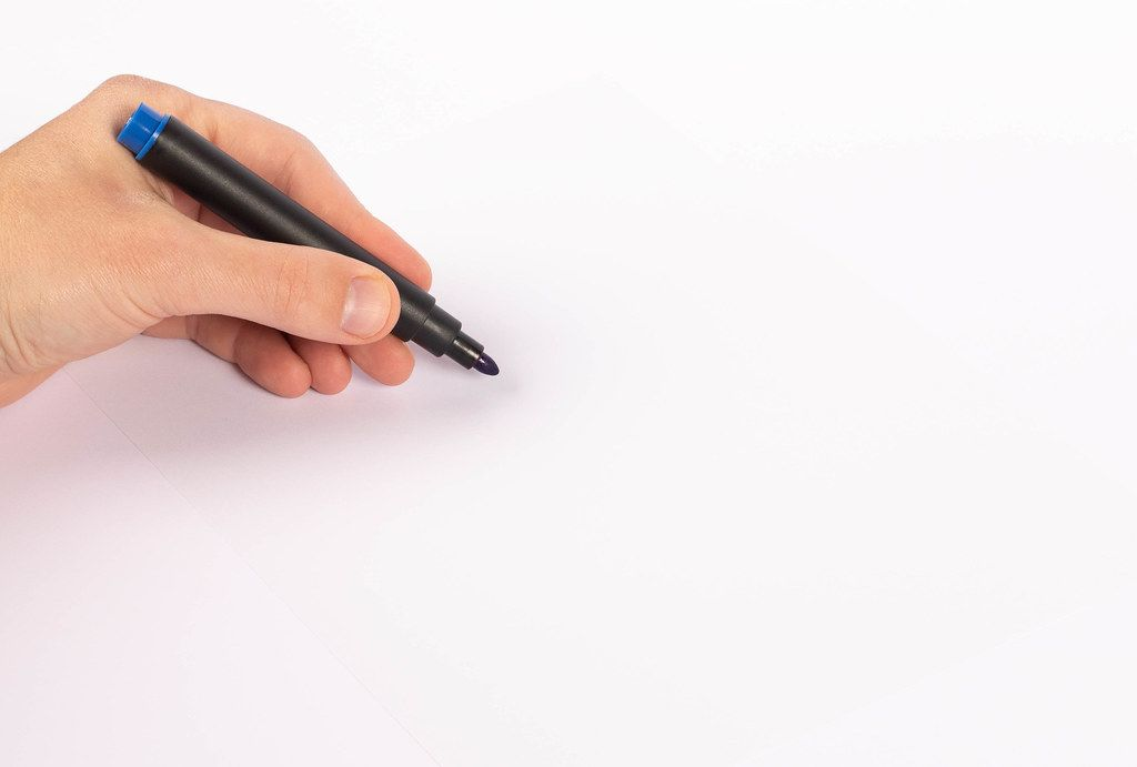 Man writing with blue pen marker on white paper (Flip 2019)