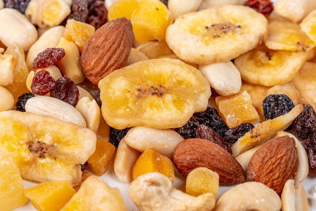 Mandeln, Erdnüsse, Cashewnüsse, Rosinen und getrocknete Bananen mit kandiertem Obst im Hintergrund