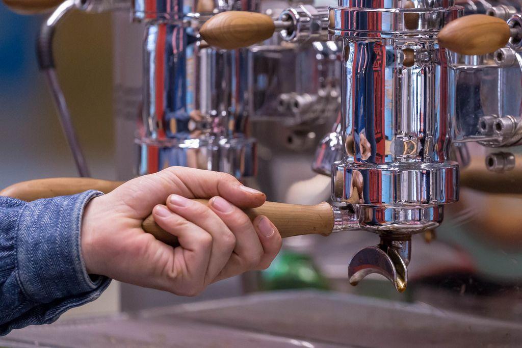 Mann bedient eine Espressomaschine