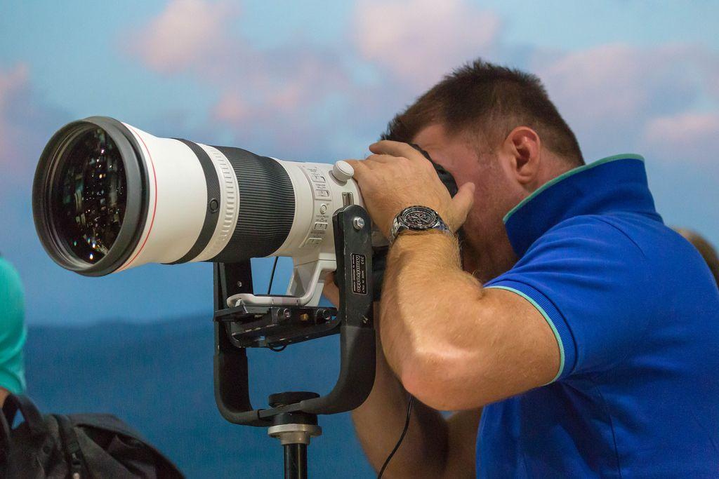 Mann blickt durch Tele-Objektiv an der Photokina in Köln