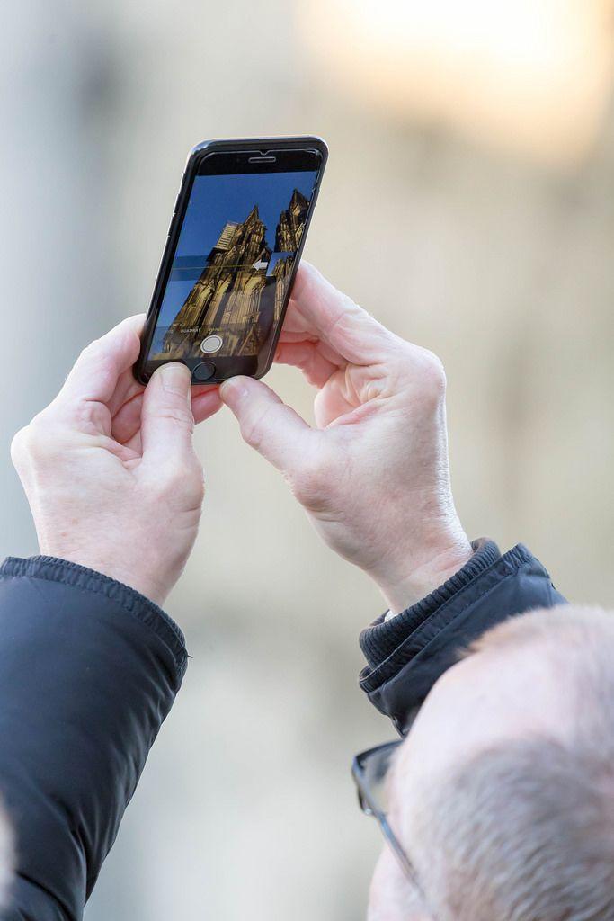 Mann fotografiert den Kölner Dom mit seinem iPhone