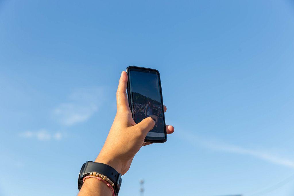 Mann fotografiert Fußballfans mit seinem Handy