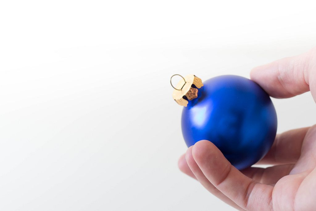 Mann hält blaue Weihnachtsbaumkugel in der Hand