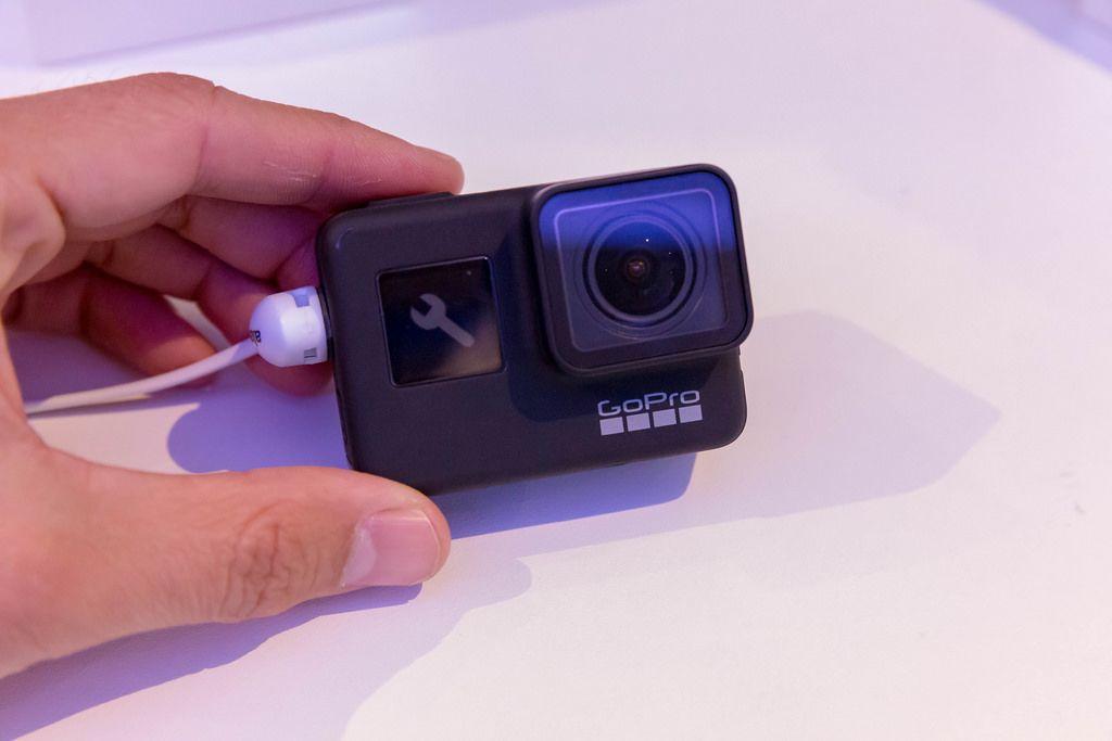 Mann hält die neue Action Kamera GoPro Hero 7 Black an der Photokina in Köln