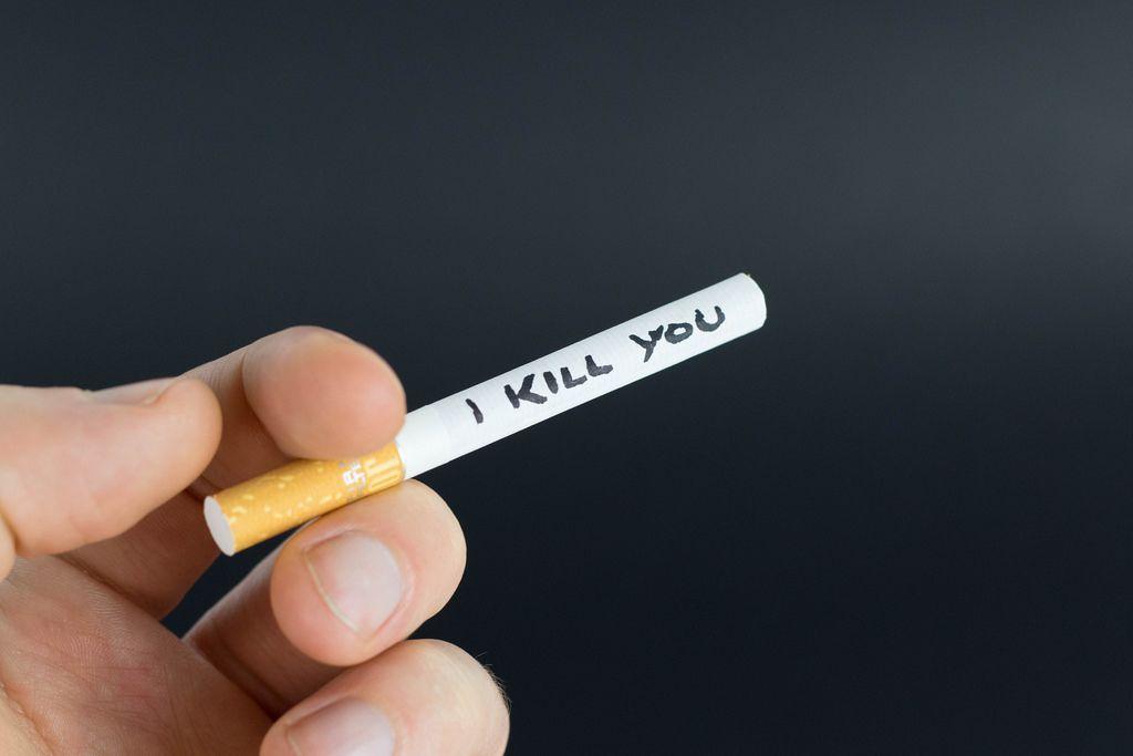 Mann hält eine Zigarette zwischen den Fingern