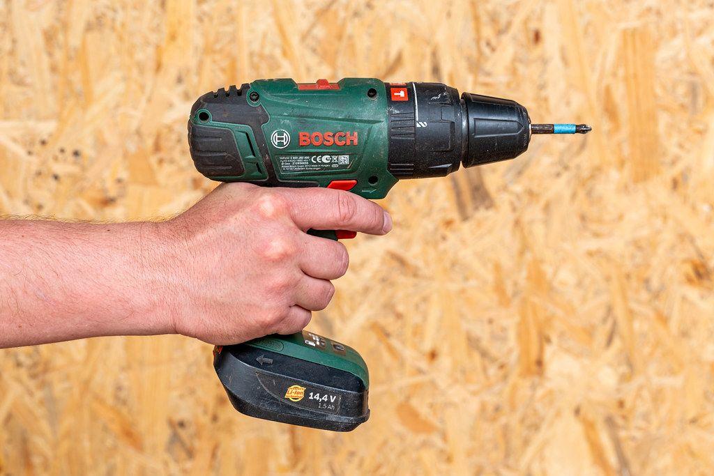 Mann hält in der Hand einen Akkuschrauber von Bosch, vor einer OSB Platte im Hintergrund